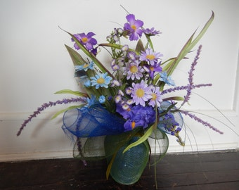 Purple & Blue flowers in a Vase wrapped in Royal Blue and Hunter Green Décor Mesh and tied with an Olive Green Velvet Ribbon