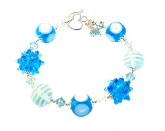 Brillant shades of blue lampwork bracelet  with genuine blue and clear Swarovski crystals, Sterling Silver heart clasp