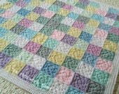 Hand made crocheted baby blanket edged in white with delicate shades of lemon lilac and duck egg
