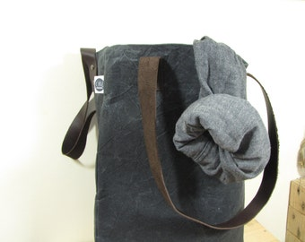 Black tote bag made with waxed canvas and genuine leather handles, lined with black cotton