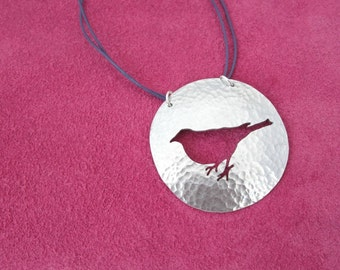 Textured disc necklace with bird silhouette