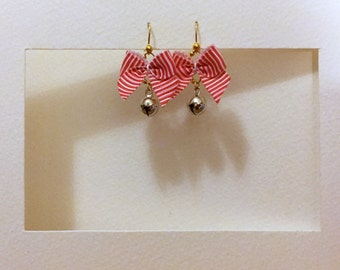 silver bell earrings swinging from white and red striped bows
