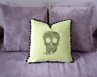Green cushion with mexican skull and pompoms