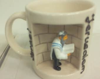 A cup of coffee with a statue An Jew with Torah
