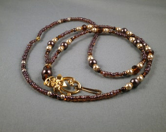 """Brown and tan pearls ID lanyard  with gold plated metal flower ,beads and ID holder . Your choice of clasp and lenght 32"""" to 42"""""""