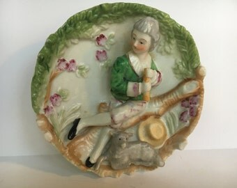 Gorgeous Vintage Colonial Wall Plaque.  Hand Painted Porcelain Plaque w/ 3D Colonial Gentleman playing a Flute w/lamb at his feet.