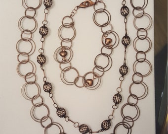 Airy copper multi-link bracelet with heart charms.