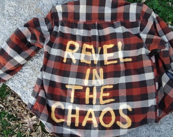 Revel In The Chaos bleached onto back of repurposed brown flannel shirt