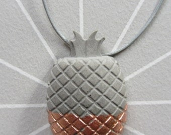 Concrete pineapples on the band necklace