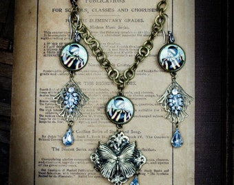 The discovery, a jewelry set of necklace and matching earrings featuring surreal circus tent girl with butterflies and rhinestone by Danita