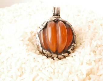 Tibetan Silver Wrapped Resin Pendant, Silver Animal Repousse Design, dark amber color carved resin.