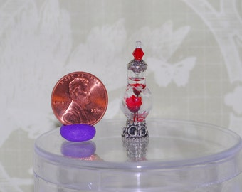 Miniature glass potion bottle with red flowers