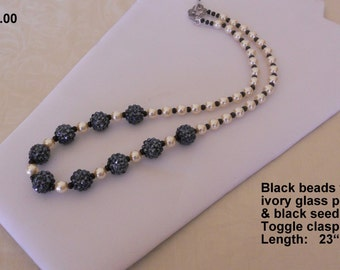 """008 ~ Necklace 23"""" long.  Creamy glass pearls with 9 accent beads of """"hematite"""" charcoal black color."""