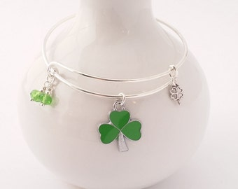 Shamrock bangle bracelet featuring shamrock and four leaf clover charms and green faceted glass beads