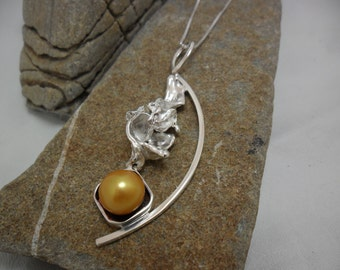 Ornate sterling silver of a yellow gold cultured pearl pendant