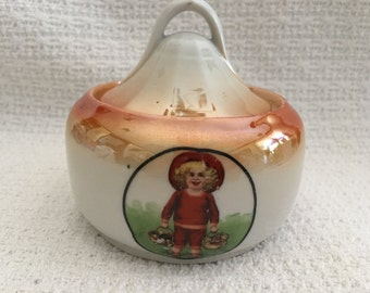 German Porcelain Lusterware Sugar Bowl, Lidded Jar, Rust on Cream, Little Blond Girl in Red with Baskets, Signed M Germany 724, 1920s, 1930s