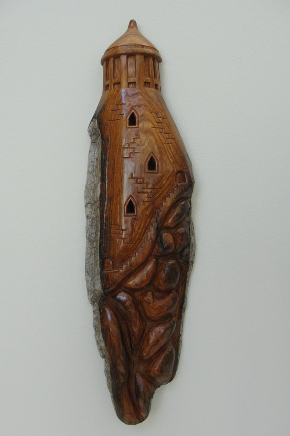 Lighthouse on the rocks in cottonwood bark wood carving