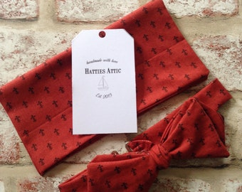 Handmade pre-tied red pointed bow tie and pocket square with a black fleur de lis pattern