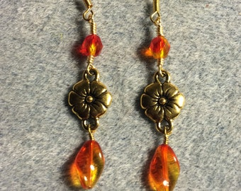 Gold Tierracast flower connector charm earrings adorned with orange yellow Czech glass twist beads and orange yellow Czech glass beads.