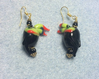 Black, green and red lampwork toucan bead earrings adorned with black Czech glass beads.