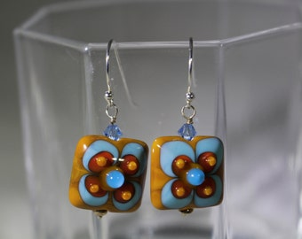 Square lampwork mustard bead with blue and red flower accent