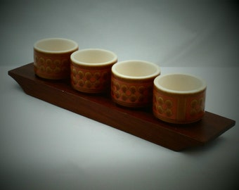A set of 4 Hornsea Pottery egg cups on a sold teak stand. Great retro design in 1970s orange and brown Saffron design.