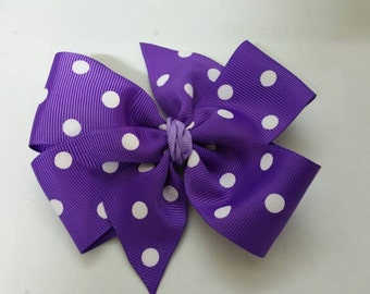 Purple polkadot pinwheel bow on a lined alligator clip