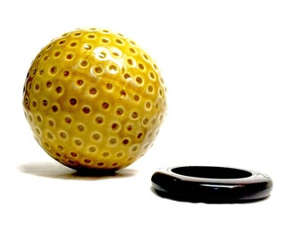 vintage golf ball paperweight on wood stand golden tone glazed pottery golf ball