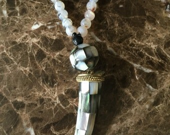 Beaded necklace with patterned horn and matching stone ball