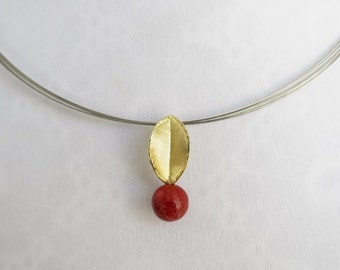 Golden pendent with coral and wire necklace.
