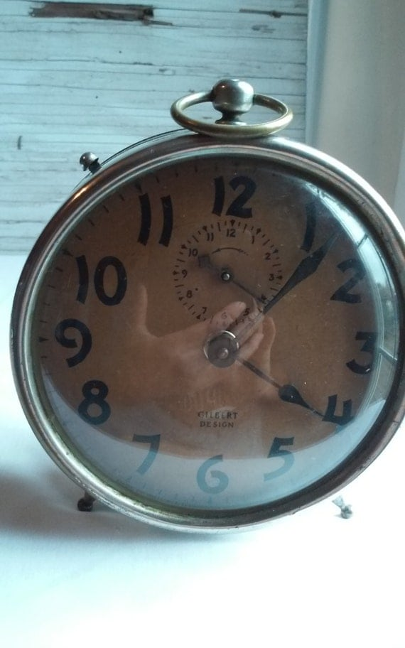 Vintage 1920s Gilbert Alarm Clock and working.  Nice Stainless steel Housing.  Clock Face Showing Age with Fading.  Great Gilbert Name.