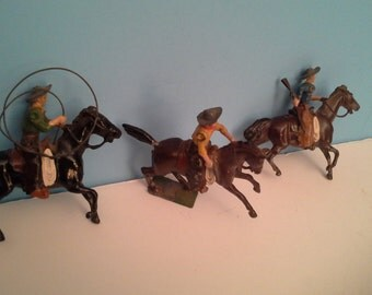3 Vintage metal cowboys on horses, 2 with moveable arms