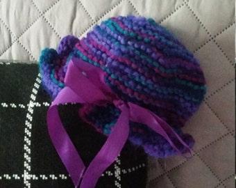 Purple and blue tye dye hand knitted baby hat with dark purple ribbon