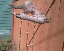 Wind chimes sun catcher hanging from a bird shaped piece of driftwood.