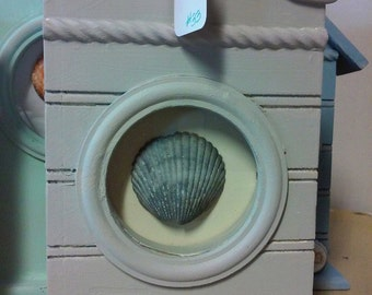 Cute gray house with seashell embellishment. Tabletop or hang. Measures 6x9x2