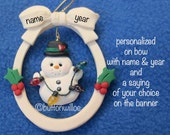 Personalized Snowman with Christmas lights inside oval ornament accented with red and green holly