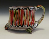 Red and lime green jagged design mug with feet