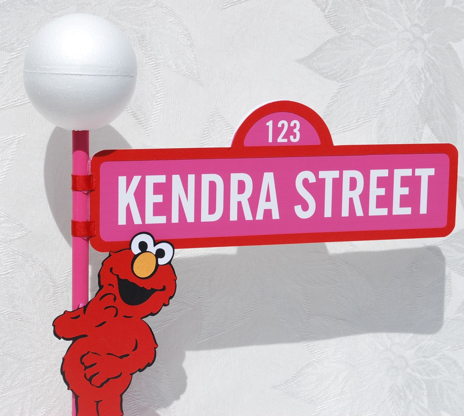 sesame street sign with lamppost and elmo character in pink