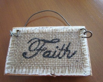 Small, Wood Sign Painted White and Distressed With The Word Faith Painted Black in a Cursive Font on Burlap with Rusty Wire Handle