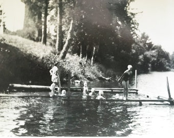 old black and white photo of kids in a lake swimming