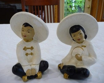 Chalkware Asian Couple Dressed With White Hats, Jackets and Black Pants