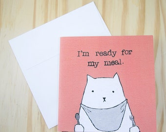 "CARD: ""Cat Demands Food"" featuring a cat in a bib, holding cutlery, and waiting impatiently to be fed"