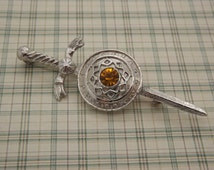A fine Celtic / Scottish sword & shield design vintage jewelry brooch in a celtic knot silvertone metal design with faceted amber stone