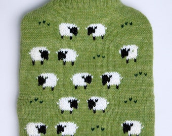 Knitted hot water bottle cover with grazing sheep design