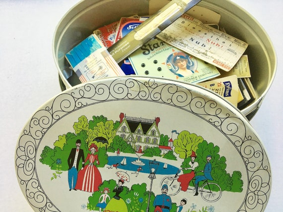 Vintage tin sewing basket packed with miscellaneous sewing notions. Thimbles. Sewing tape. Snaps and closures.