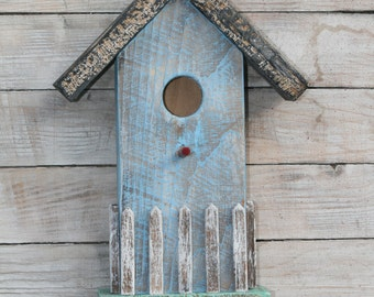A cute country style bird house with a white picket fence