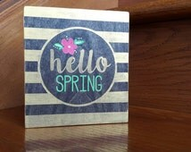 "Hello Spring. Espresso stained desk/shelf sign w/gold stripes, pink flower and gold and green wording. Approximately 6"" x 5.5"" dimensions."