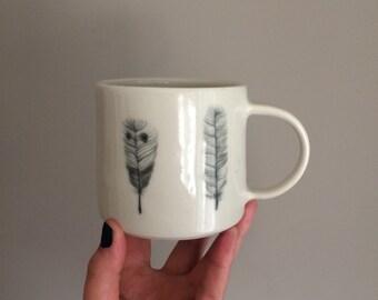 Wheel thrown porcelain mug. Hand painted feathers.