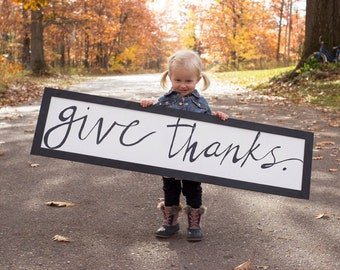 Large Give Thanks Sign. Great addition to your fall decor! White background. Black lettering. 4 ft long x 12 in wide.