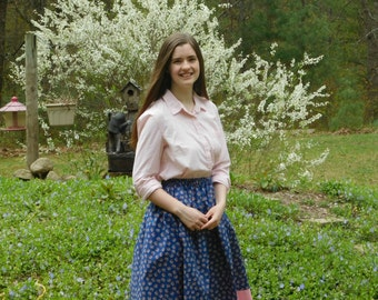 Girl's skirt, modest, with clusters of pink flowers on a blue background w/pink band at hem